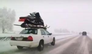 Sorpresa y desconcierto en la carretera por un coche con una moto de nieve atada en el techo